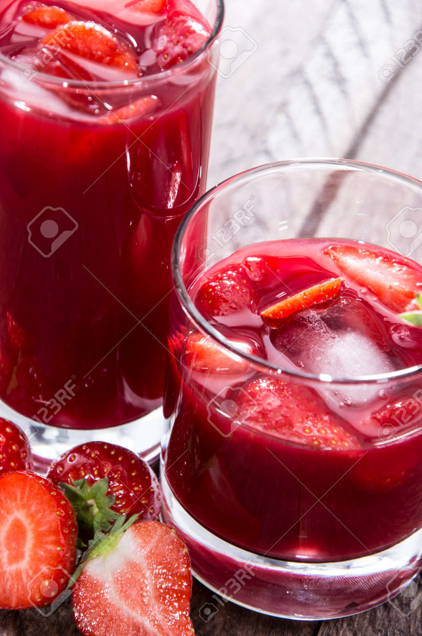 Some glasses with Strawberry Liqueur on wooden background Stock Photo - 16157739
