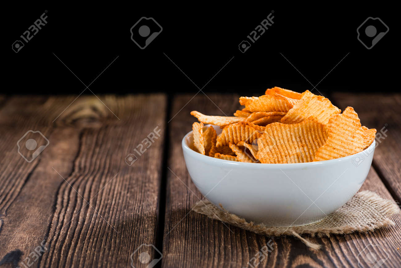 Rippled Potato Chips (selective focus) on an vintage wooden table - 53456503