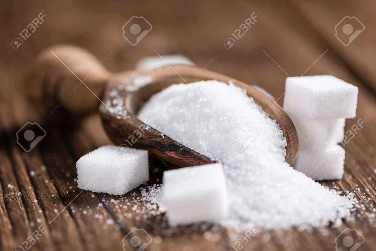 Portion of White Sugar (detailed close-up shot; selective focus) on wooden background - 54041654