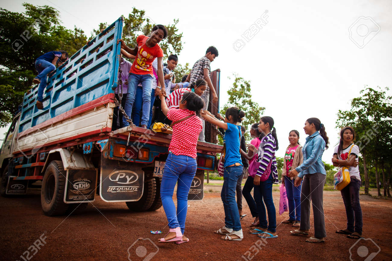 SIEM REAP, CAMBODIA - CIRCA JUNE 2012: Students hopping on a truck used as school bus June 2012 in SIEM REAP, CAMBODIA. Stock Photo - 16070042