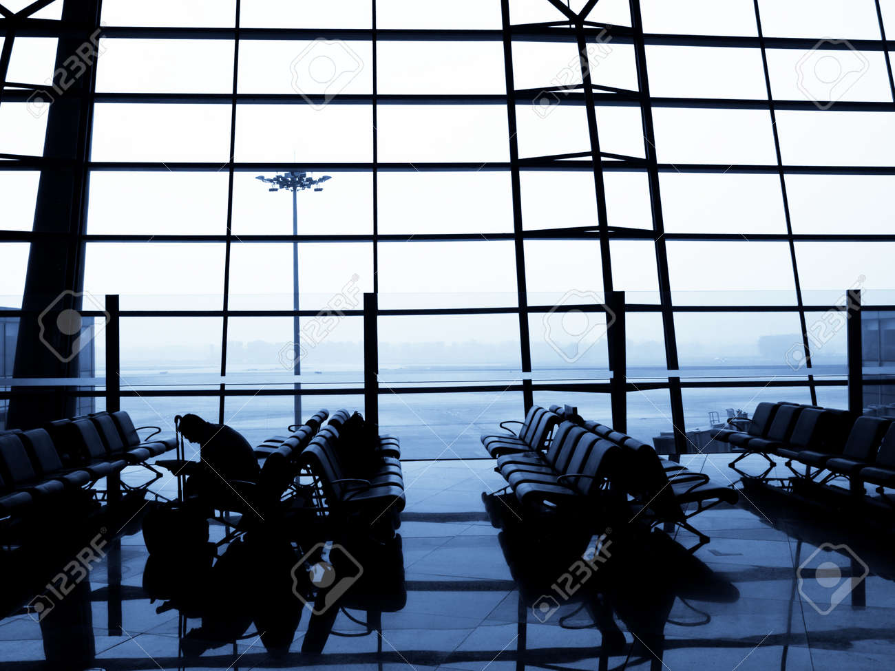 A traveller waiting for his plane at departure area. Beijing International Airport, China Stock Photo - 11147447