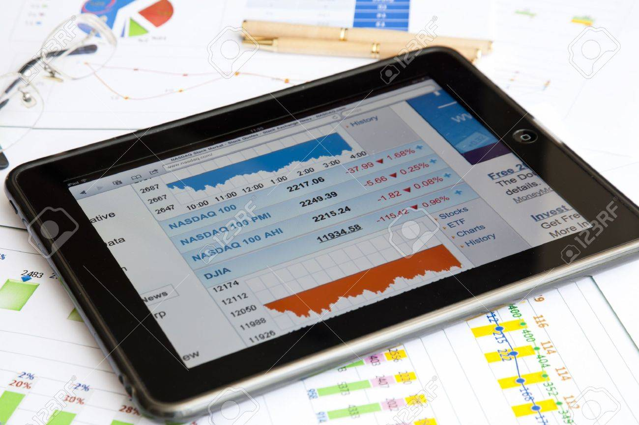 An Ipad Placed On Paper Financial Reports With Pen And Glasses ...