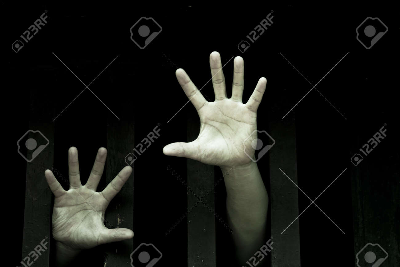 Prisoner hands stretch out from prison bars Stock Photo - 11433342