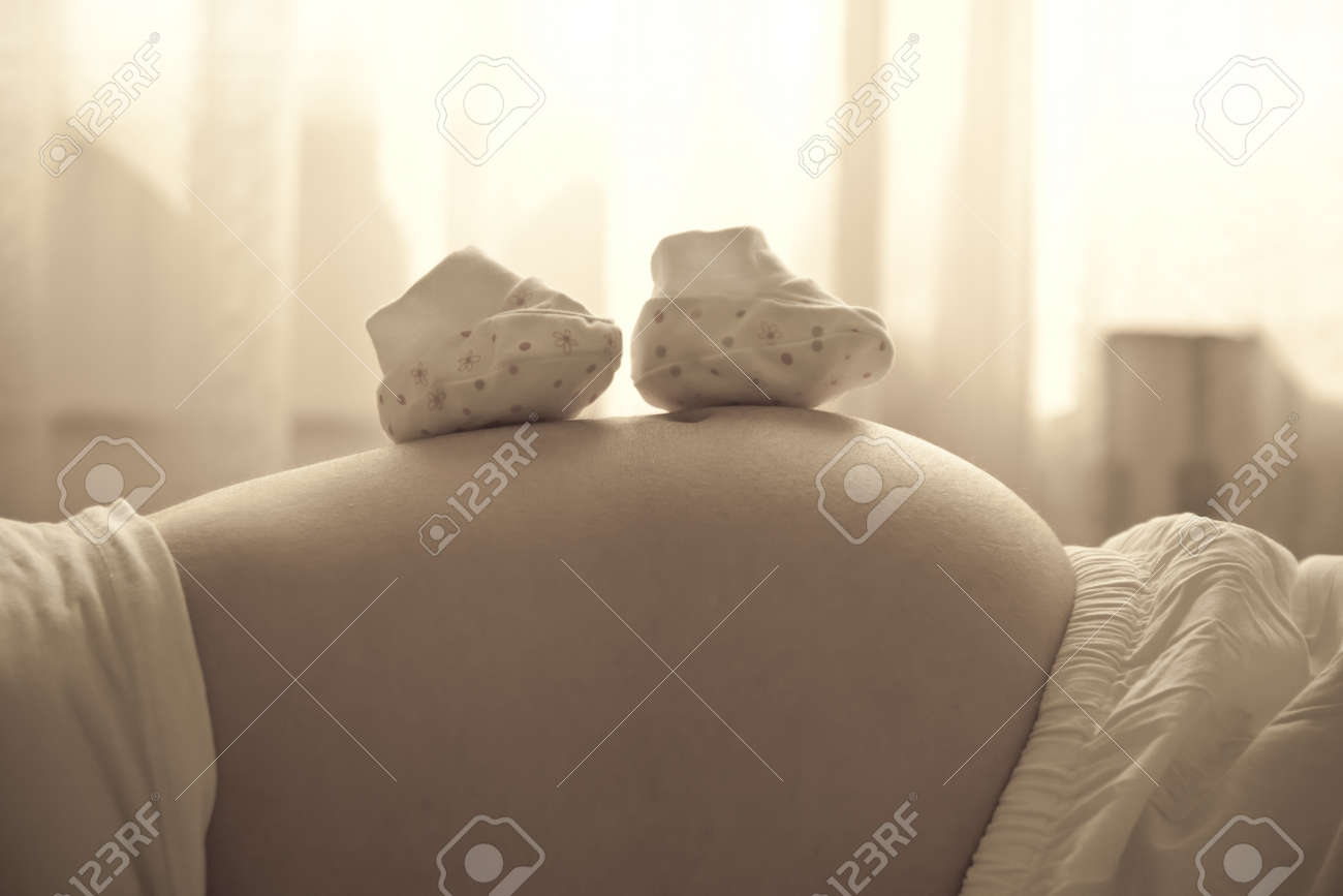 Pregnant woman with small baby shoes Stock Photo - 11552178