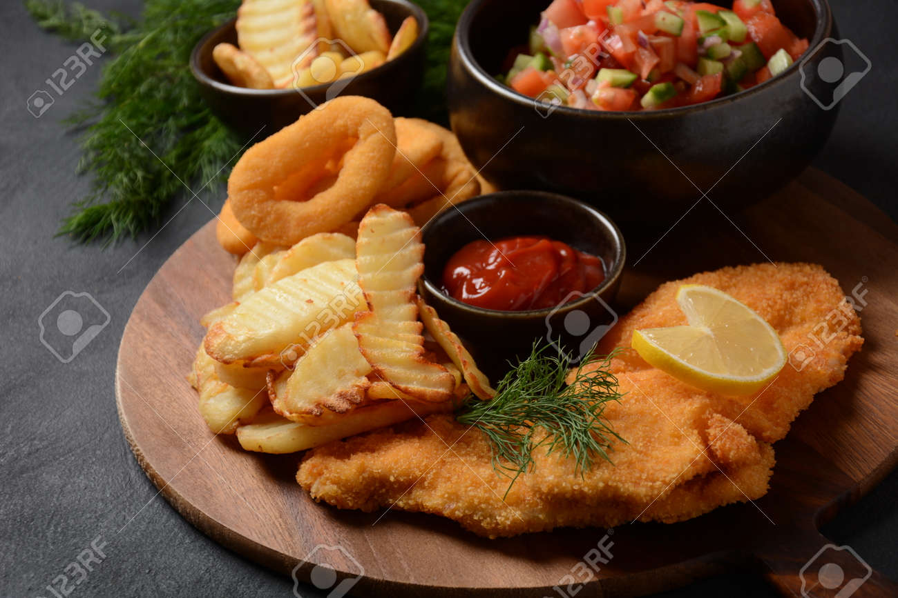 Meat schnitzel and fried potatoes with onion rings deep fried, vegetable salad - 163009332