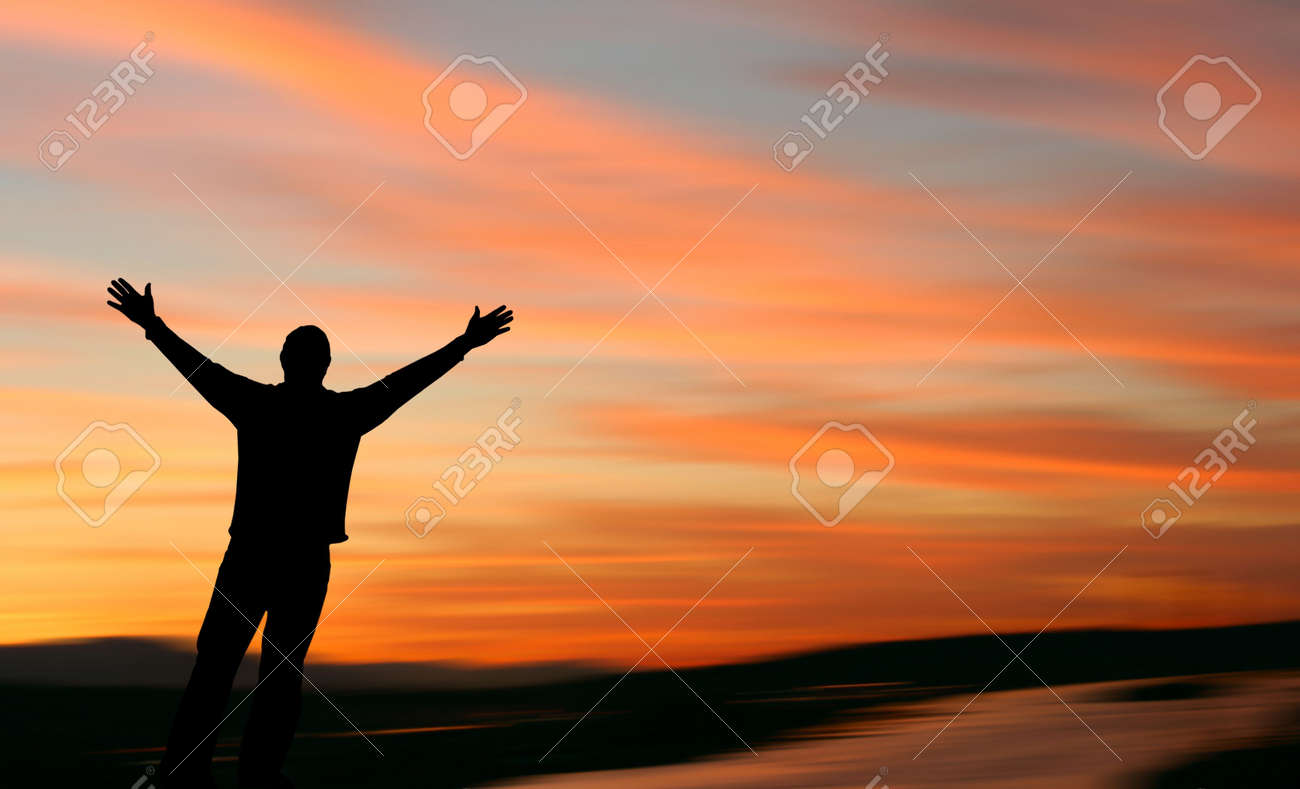 Man with outstretched arms facing a beautiful sunset. - 3204962