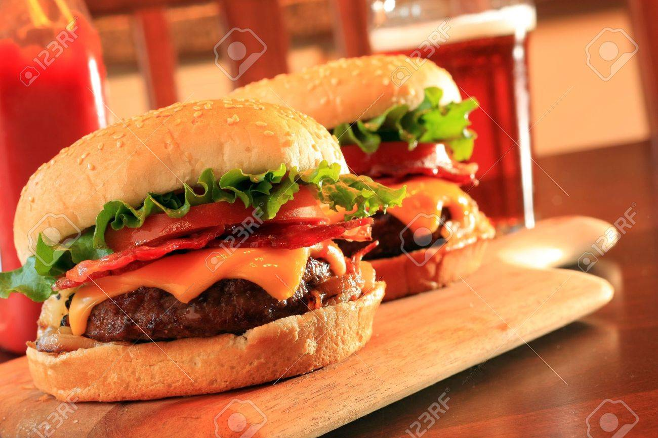 Juicy bacon cheeseburgers and beer. Stock Photo - 3331906