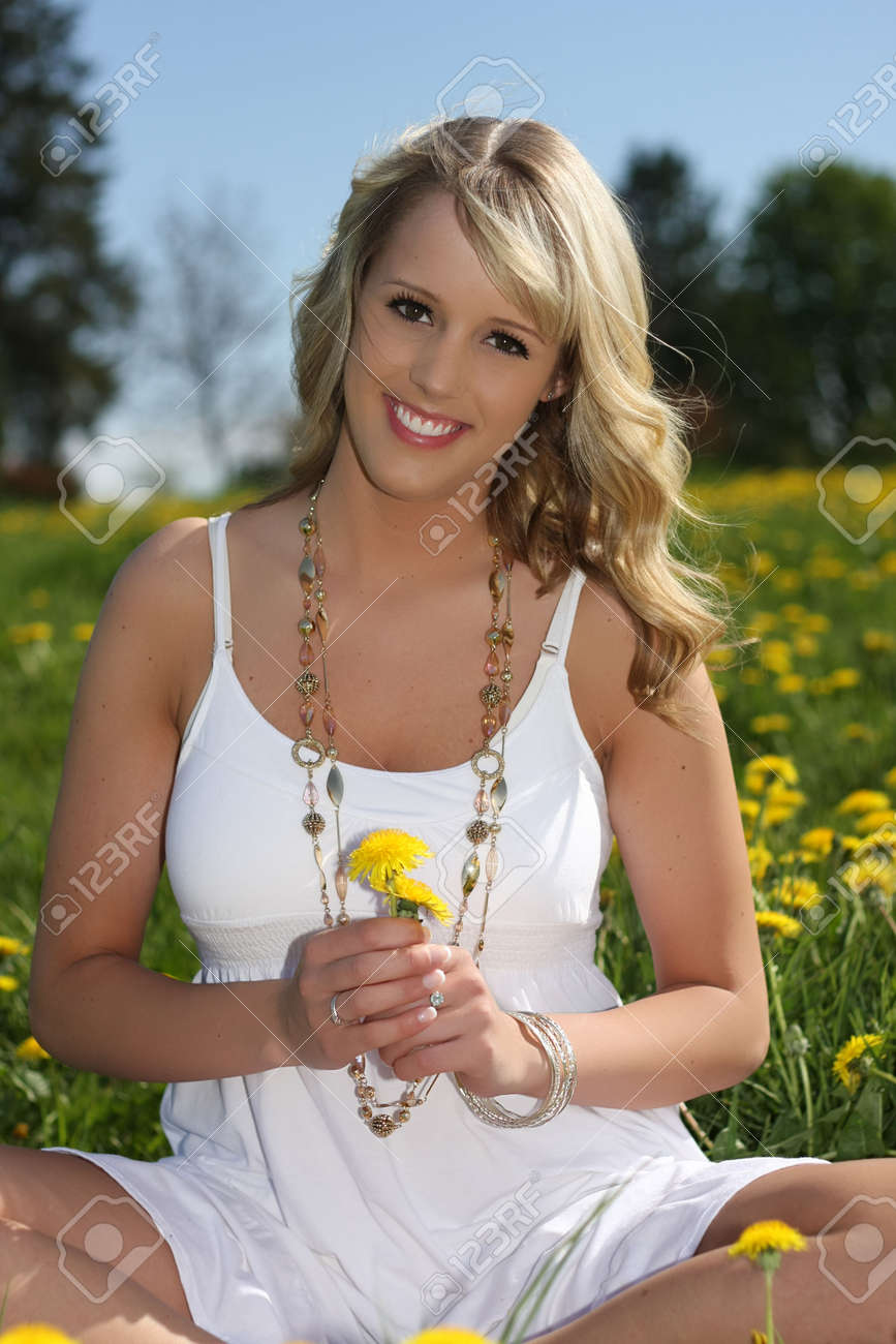 Beautiful blond girl seated in a field of wildflowers. Stock Photo - 6375563