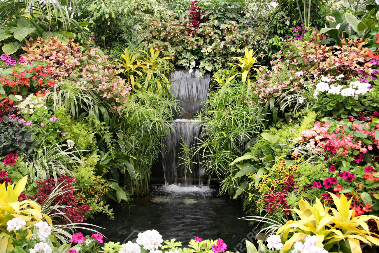 Beautiful Waterfall Garden Surrounded By Flowers Stock Photo