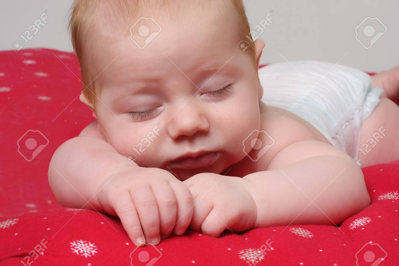 Baby boy, three month old, sleeping on a Christmas blanket. Stock Photo - 8483785