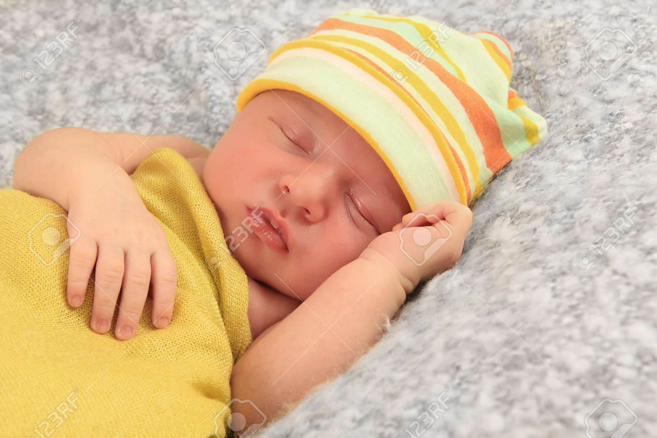 Newborn Baby Boy Asleep Wrapped In A Yellow Blanket Stock Photo