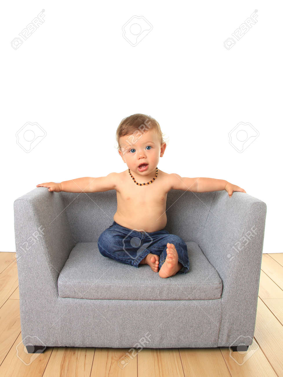 Adorable Ten Month Old Baby Boy Seated On A Sofa Chair Stock Photo
