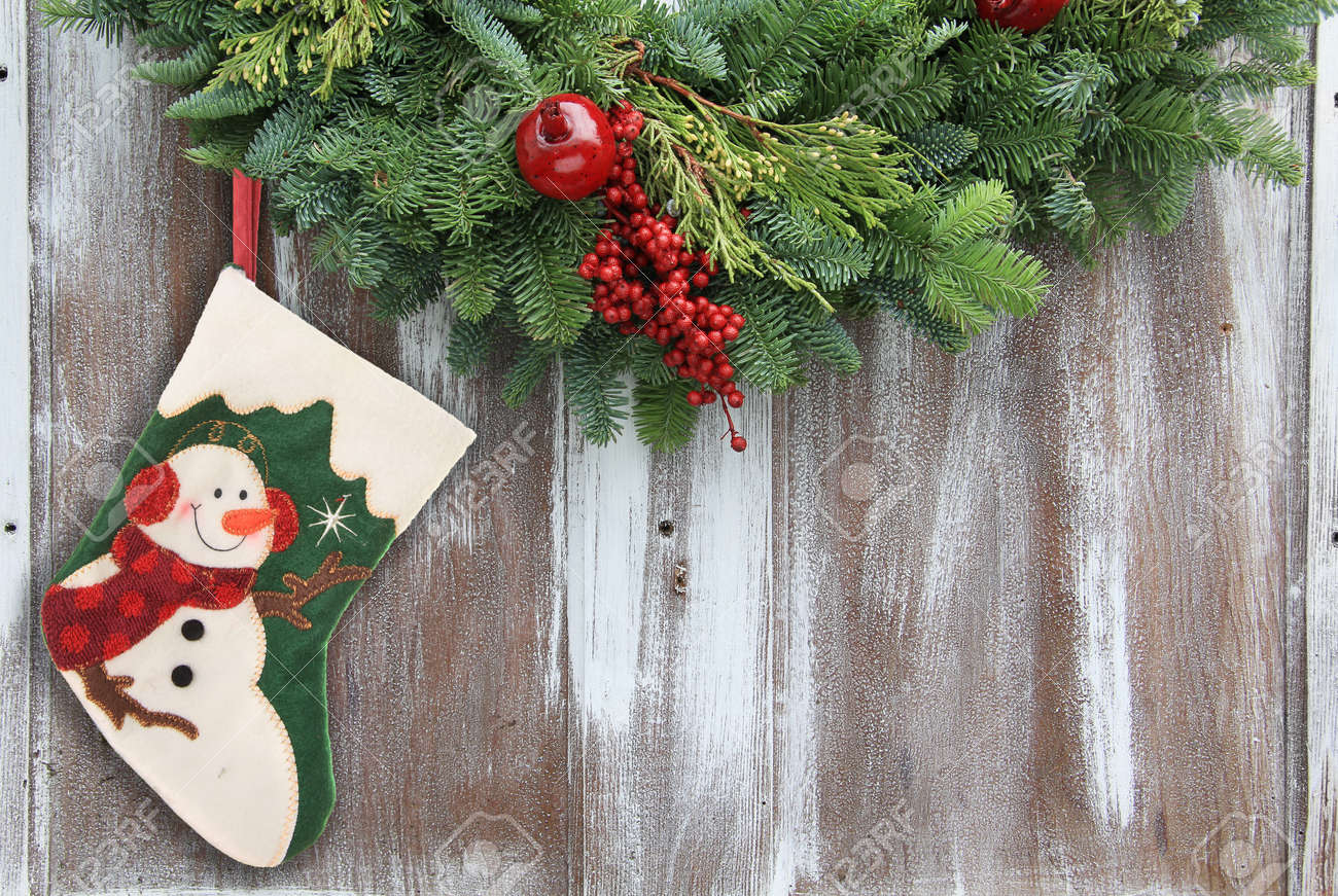 Christmas garland with a snowman stocking on a rustic wooden background. Stock Photo - 16505796