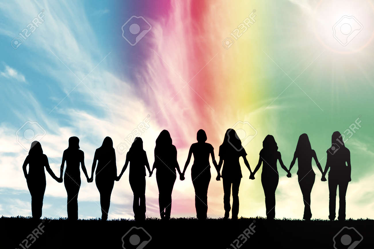 Silhouette of ten young women, walking hand in hand under a rainbow sky. - 60214177