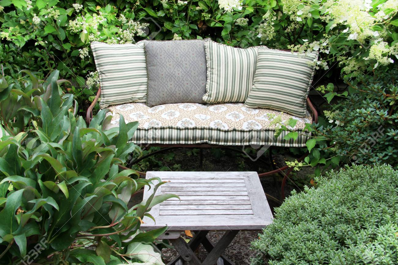 Excellent Cozy Garden Lounge Chair With Pillows Surrounded By Green Shrubs Cjindustries Chair Design For Home Cjindustriesco