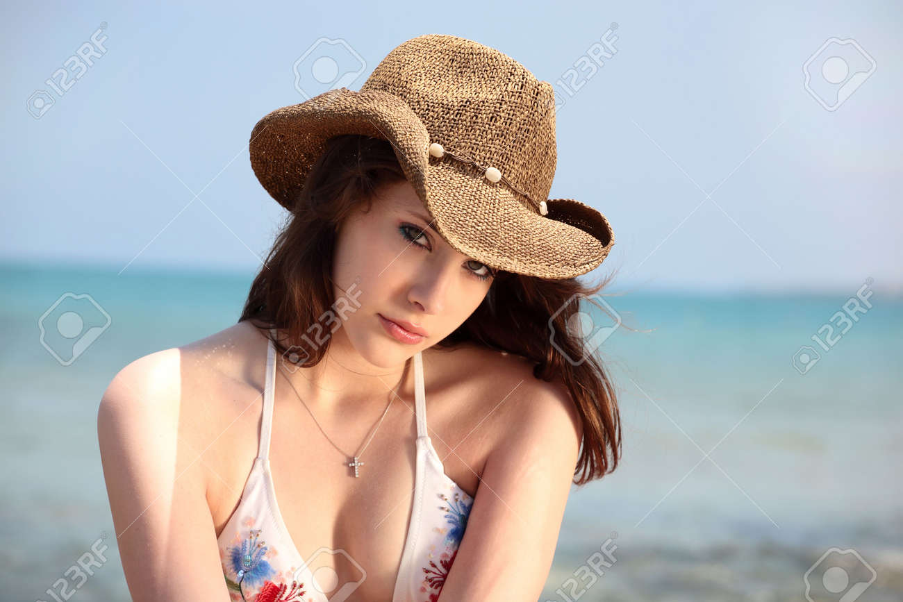 5dc3d40afee0c beautiful teen girl in swimwear and cowboy hat on the beach Stock Photo -  3095277