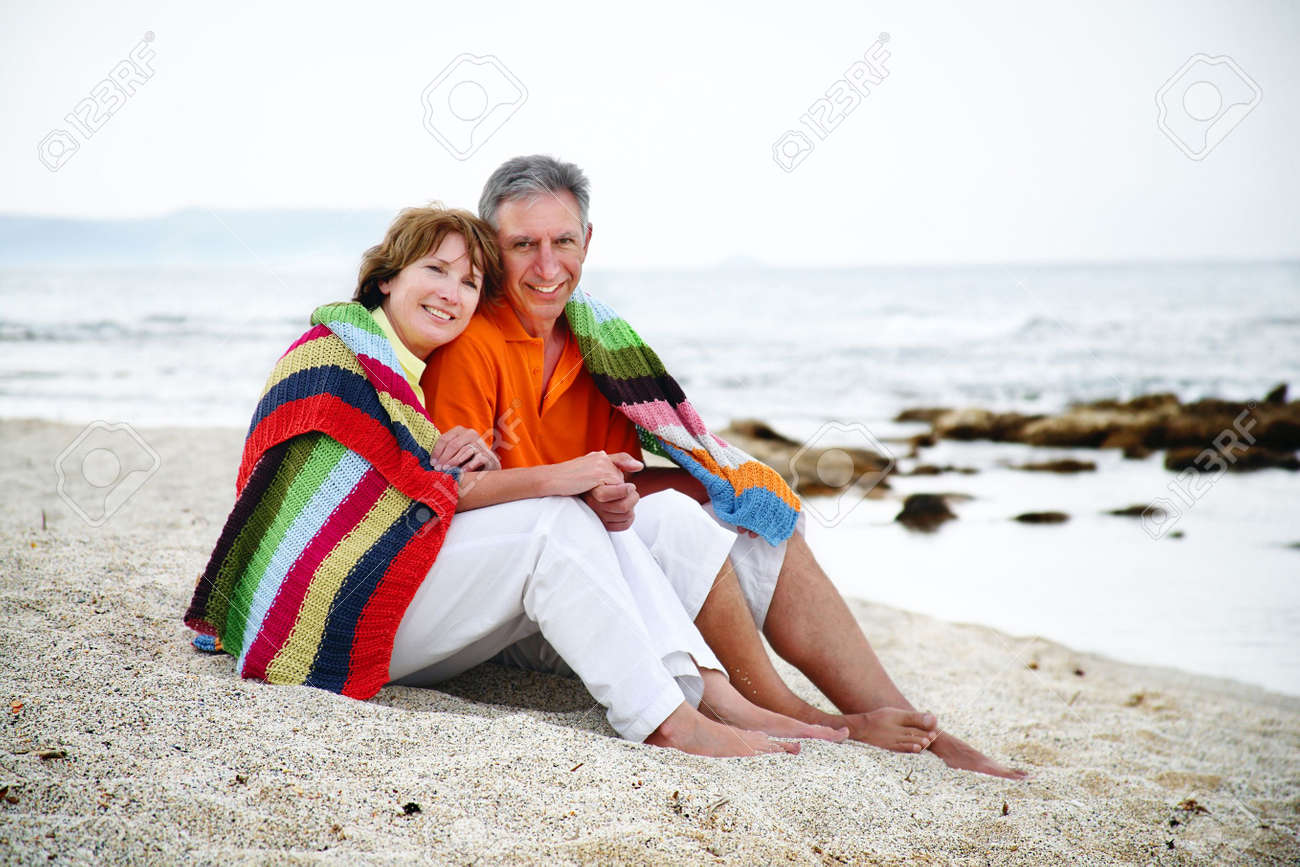 Happy mature couple sitting on the beach. - 6428670