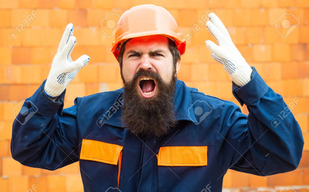 Angry builder. Incident at a construction site. Safety rules for builders. Bearded man in helmet on the construction of a new building. - 125829419