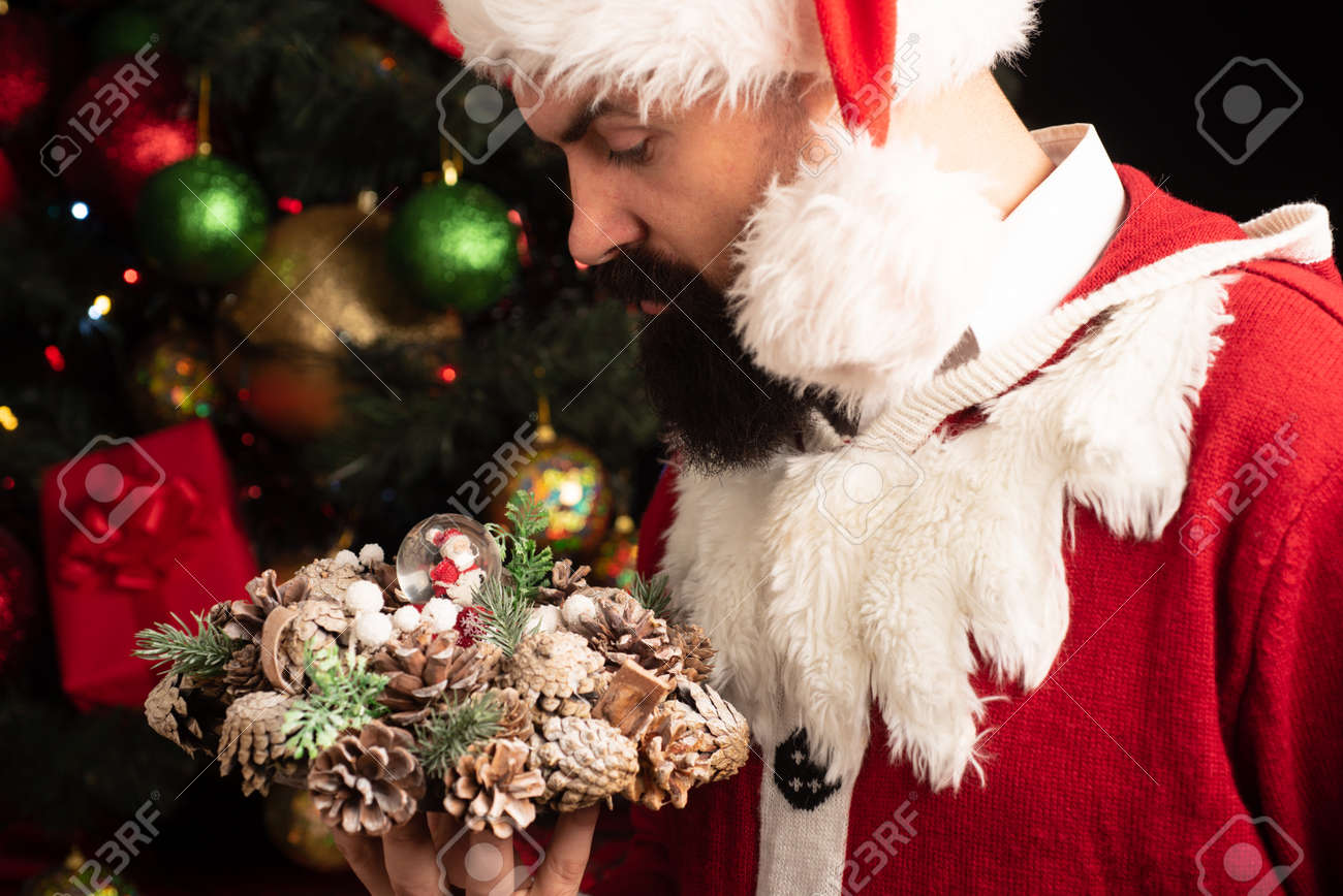 Santa with Christmas decorations. Attractive man holding a christmas wreath in his hands. Holidays. - 135514655