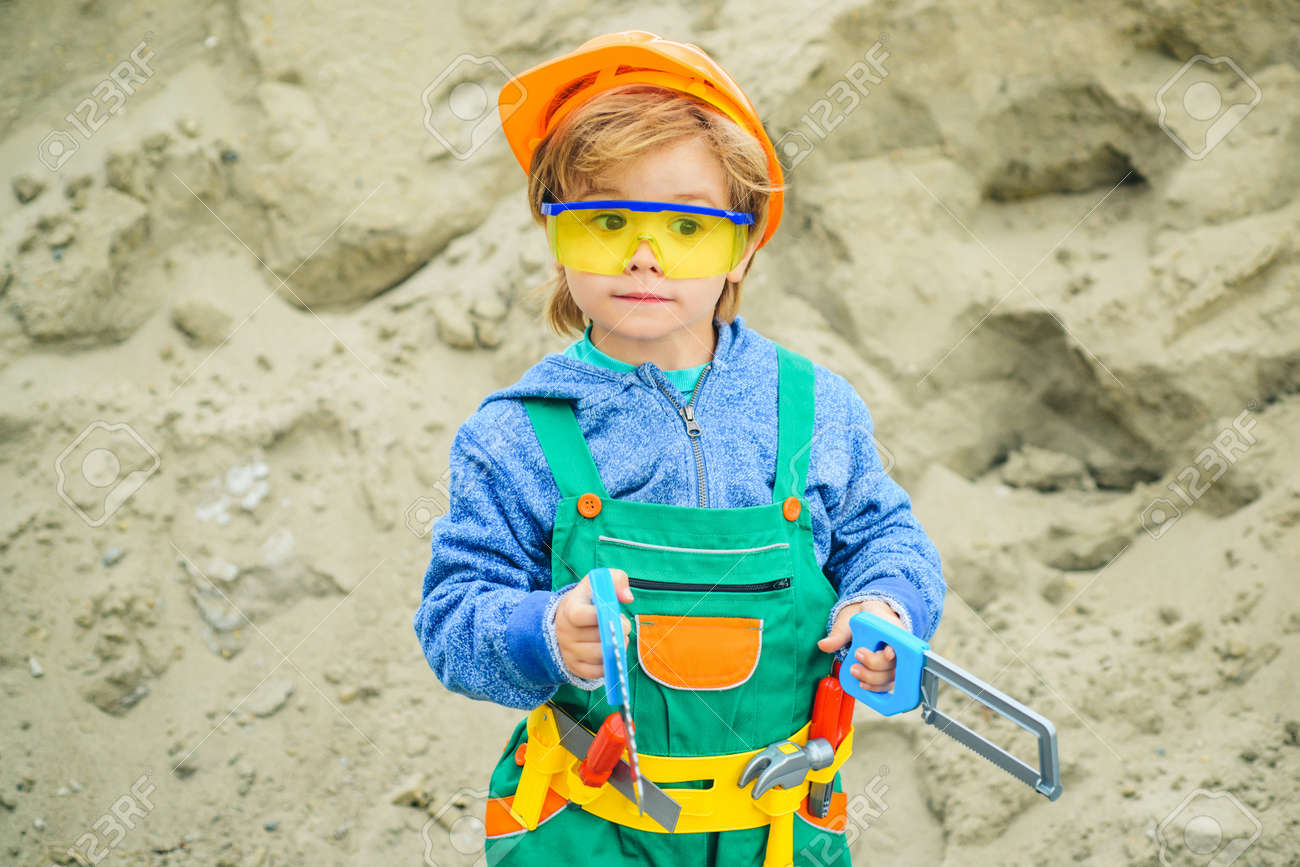 Builder. The boy in the costume of the builder. Tools for building and repair. Safety glasses and hard hat. Safety at work. Child Builder repairman. Future engineer. - 163244707