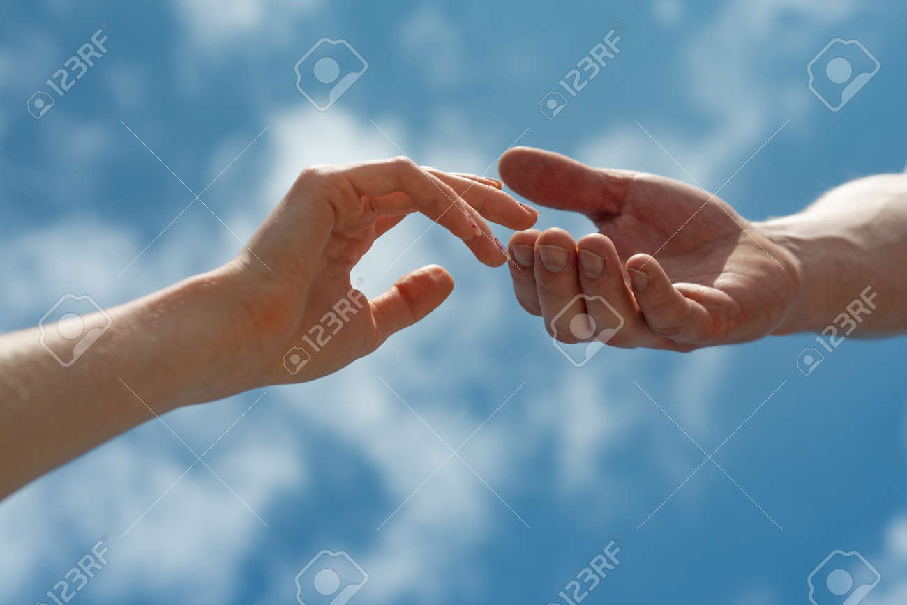 Hands on sky background. Couple, love, together. - 165065814