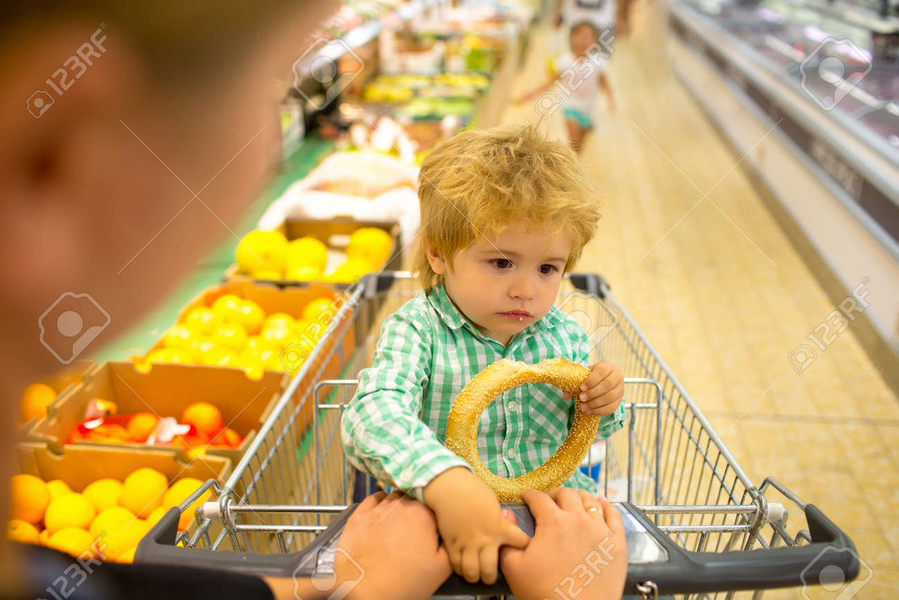 Shopping with mom. Child at the supermarket. Snack. - 163411714