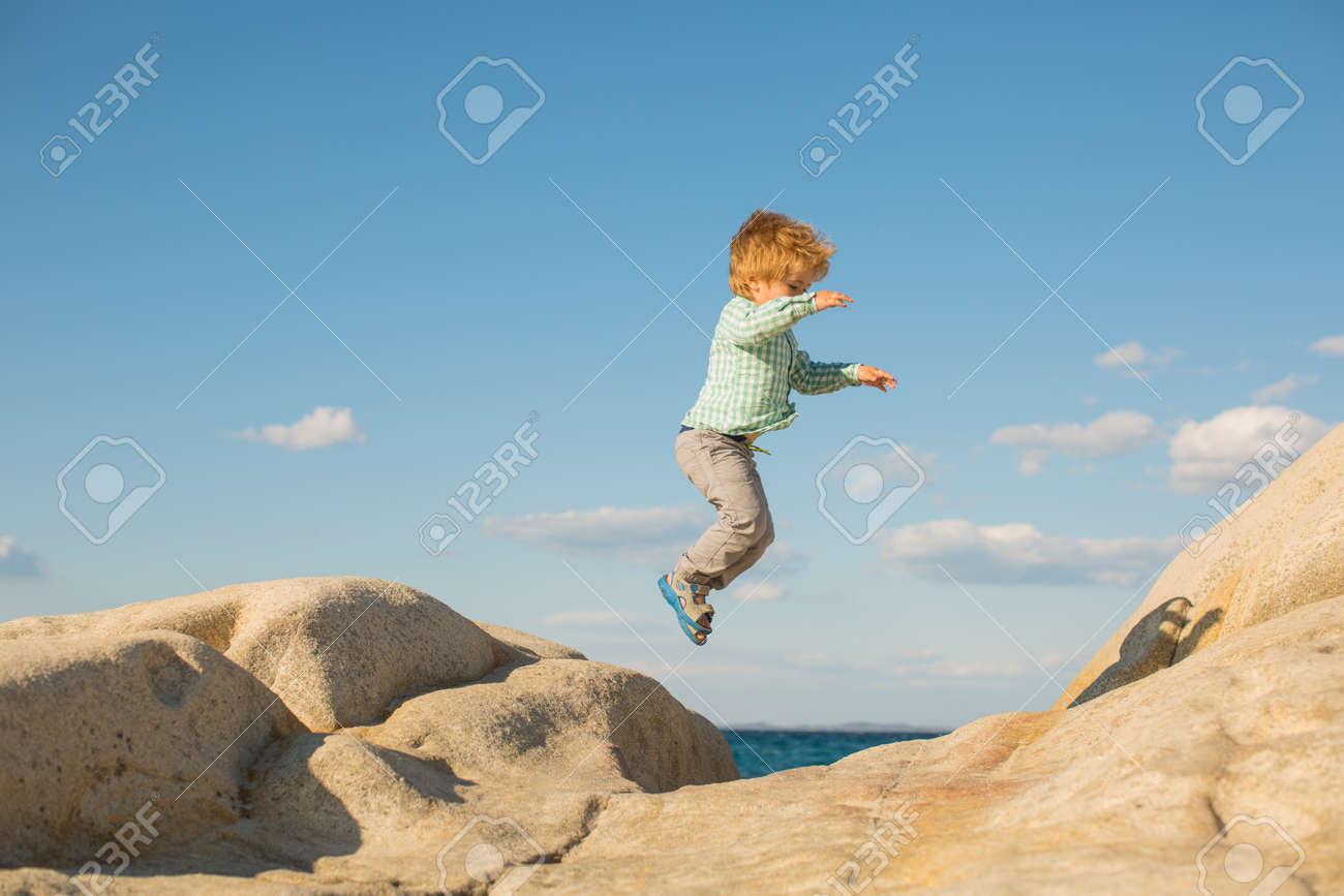 Happy jump. Children holidays at the beach. - 163411715