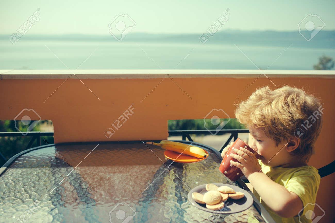 Breakfast. Milk with cookies. Child on summer vacation near sea. - 163411717