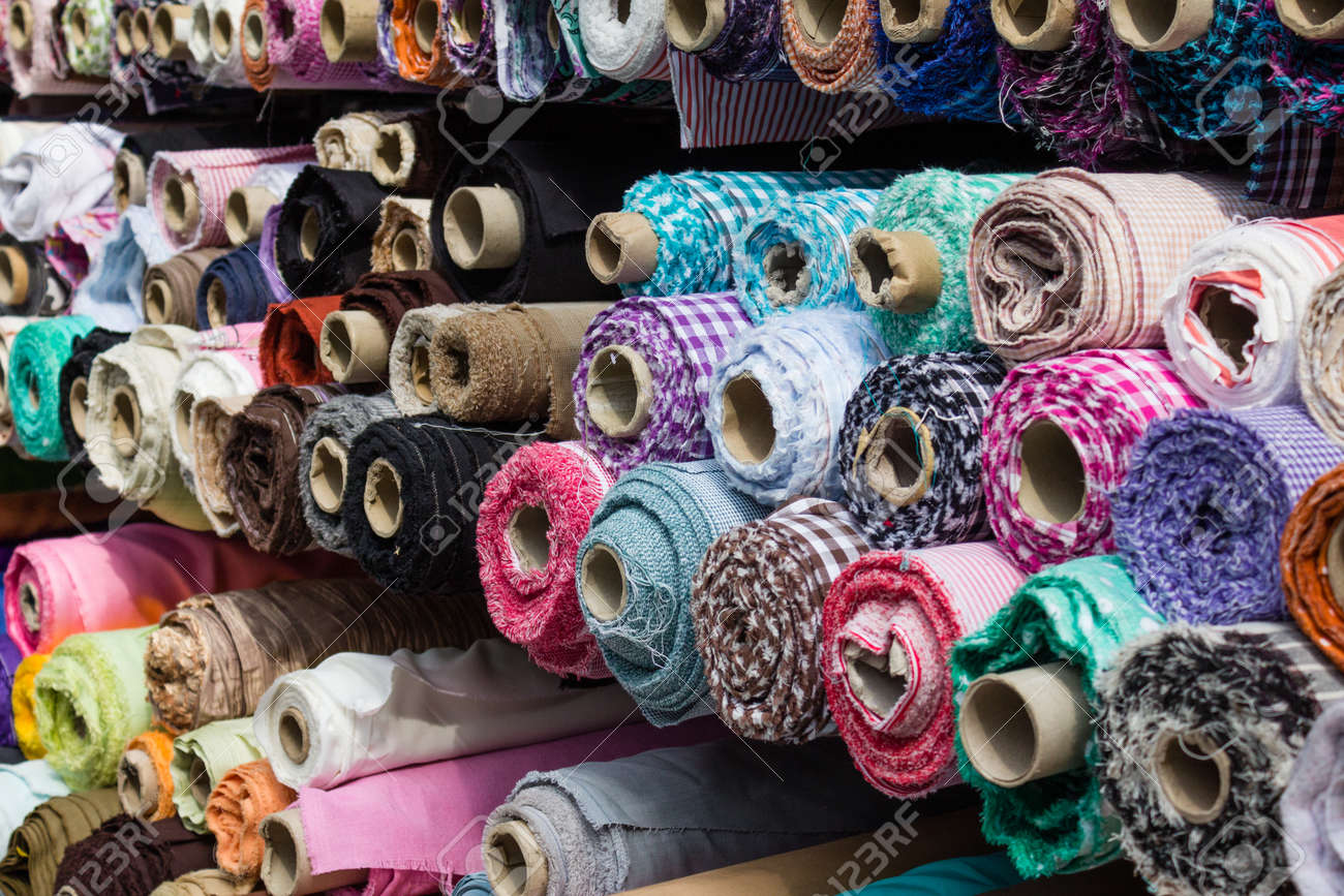 fabric rolls at market stall - textile industry background - 60397075