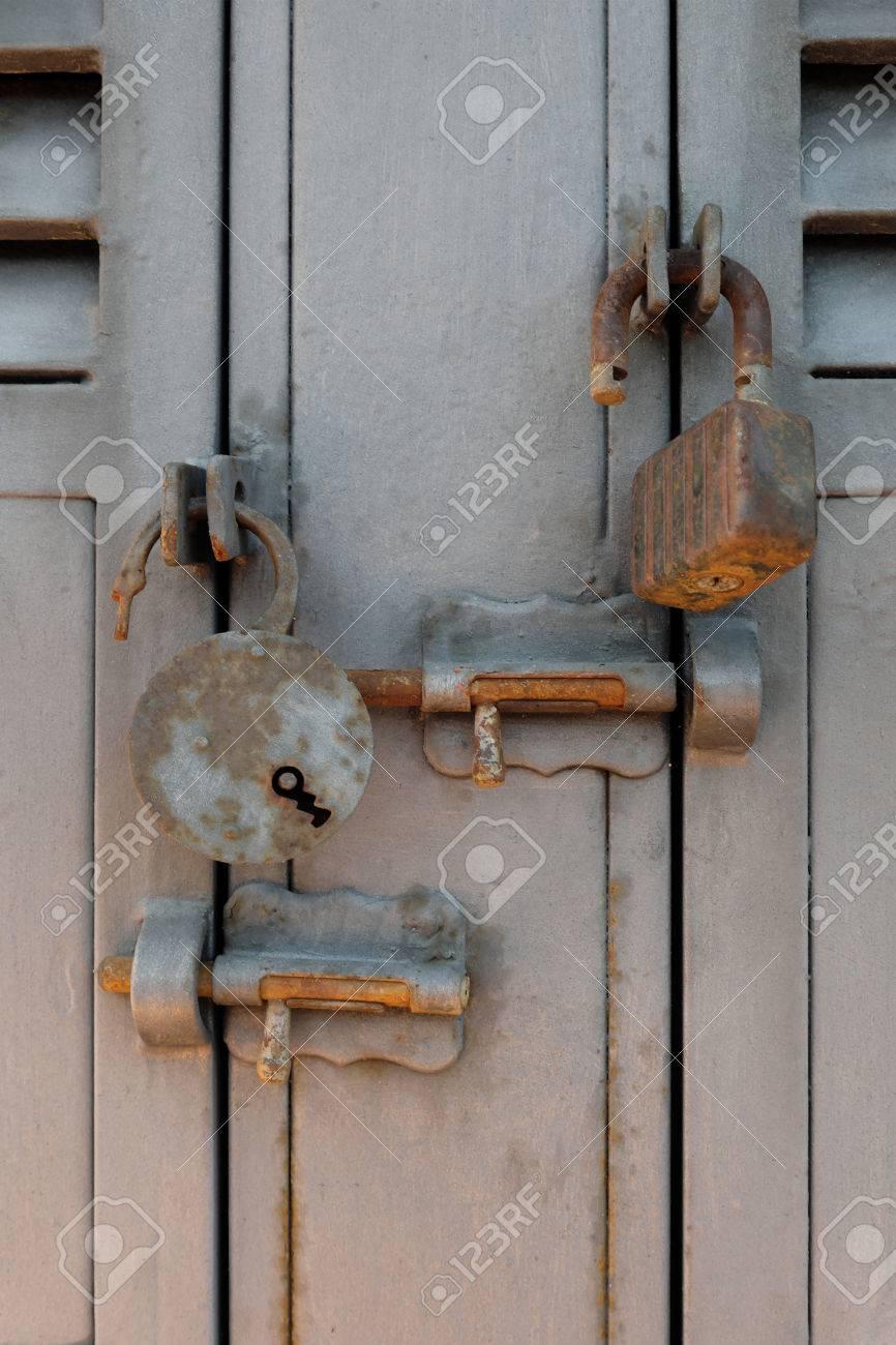 rusty old padlocks and locking bolts on metal doors