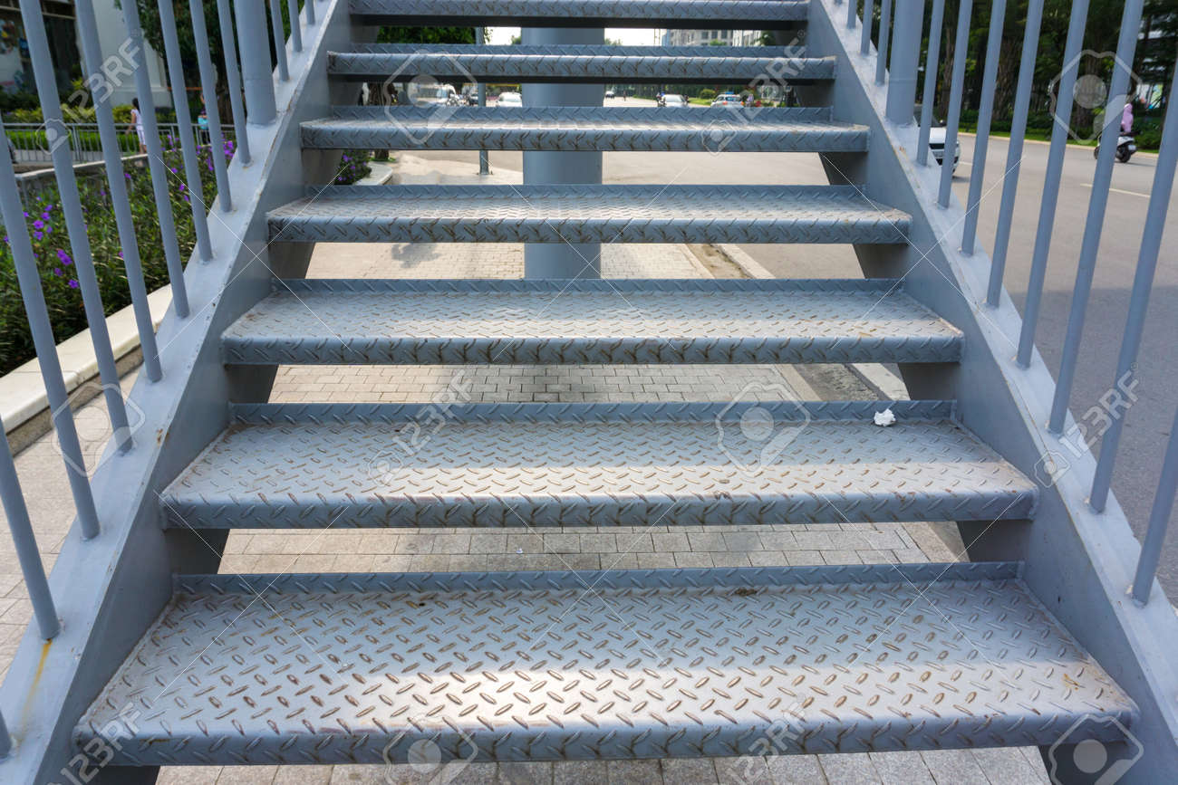 Steel stair step to walk up or walk down to the outdoor public bridge - 121049828