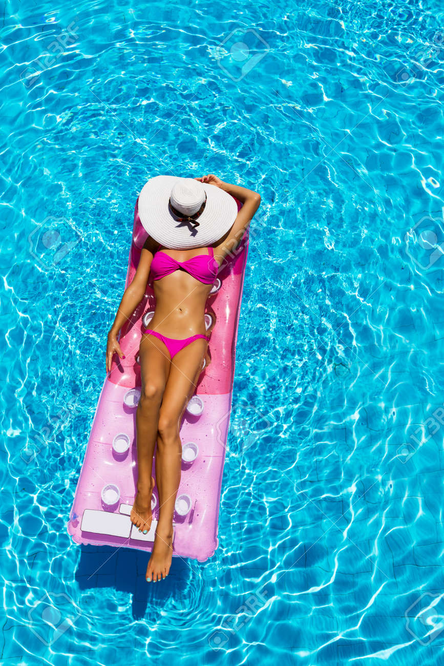 Sexy Woman Takes A Sunbath On Float In The Pool Aerial Shot Stock Photo