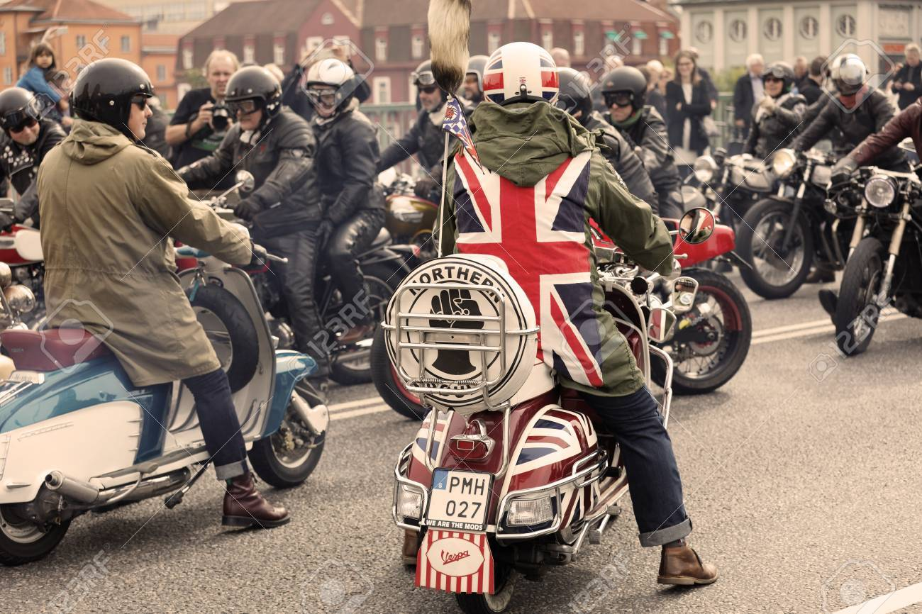 STOCKHOLM, SWEDEN - SEPT 02, 2017: Mods wearing uk flag and rockers wearing leather clothes driving retro vespa scooters and mc at the Mods vs Rockers event at the Saint Eriks bridge, Stockholm, Sweden, September 02, 2017 - 87459376