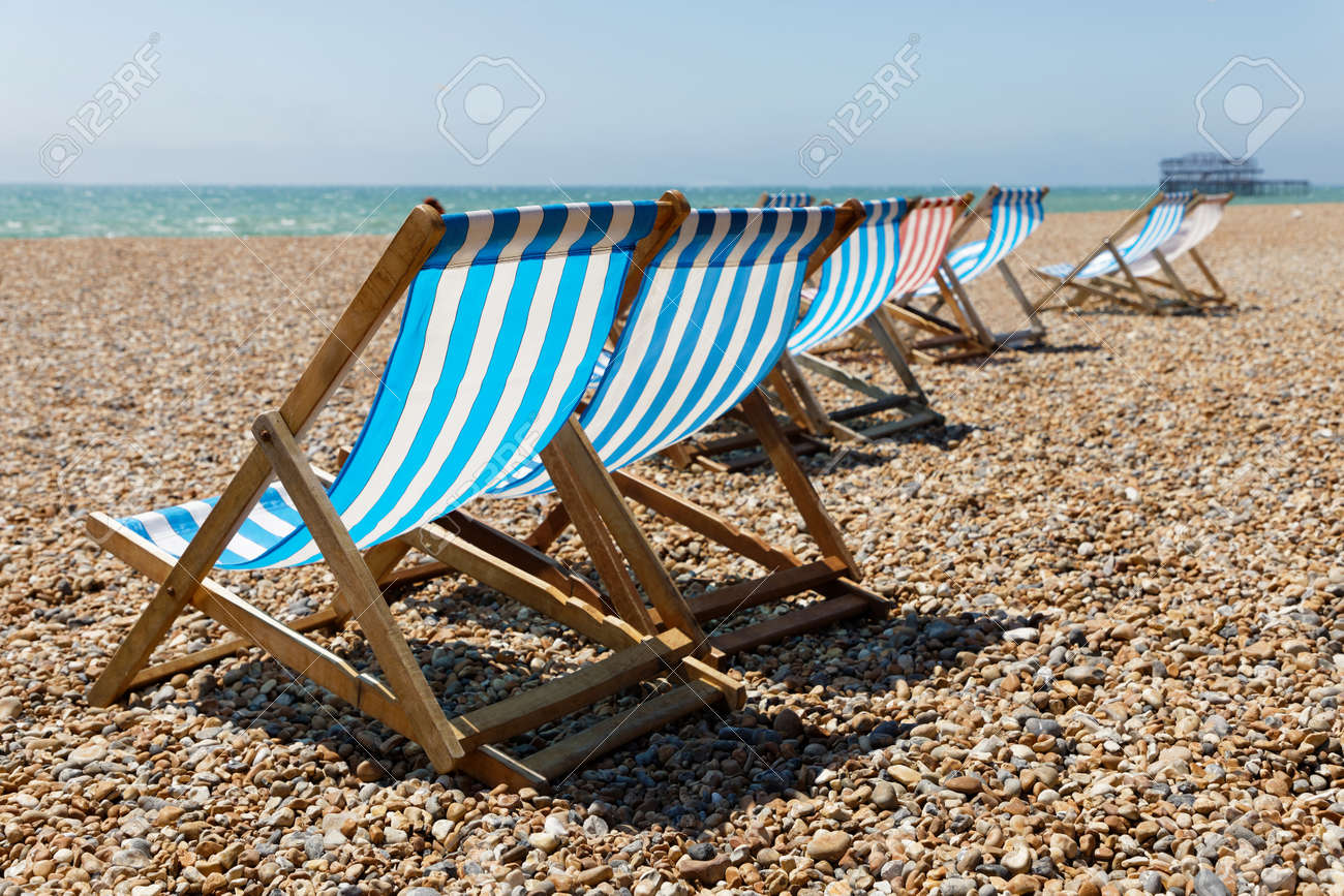Classic Blue, Red And White Striped Empty Deckchairs On The Beach. The Old  Pier
