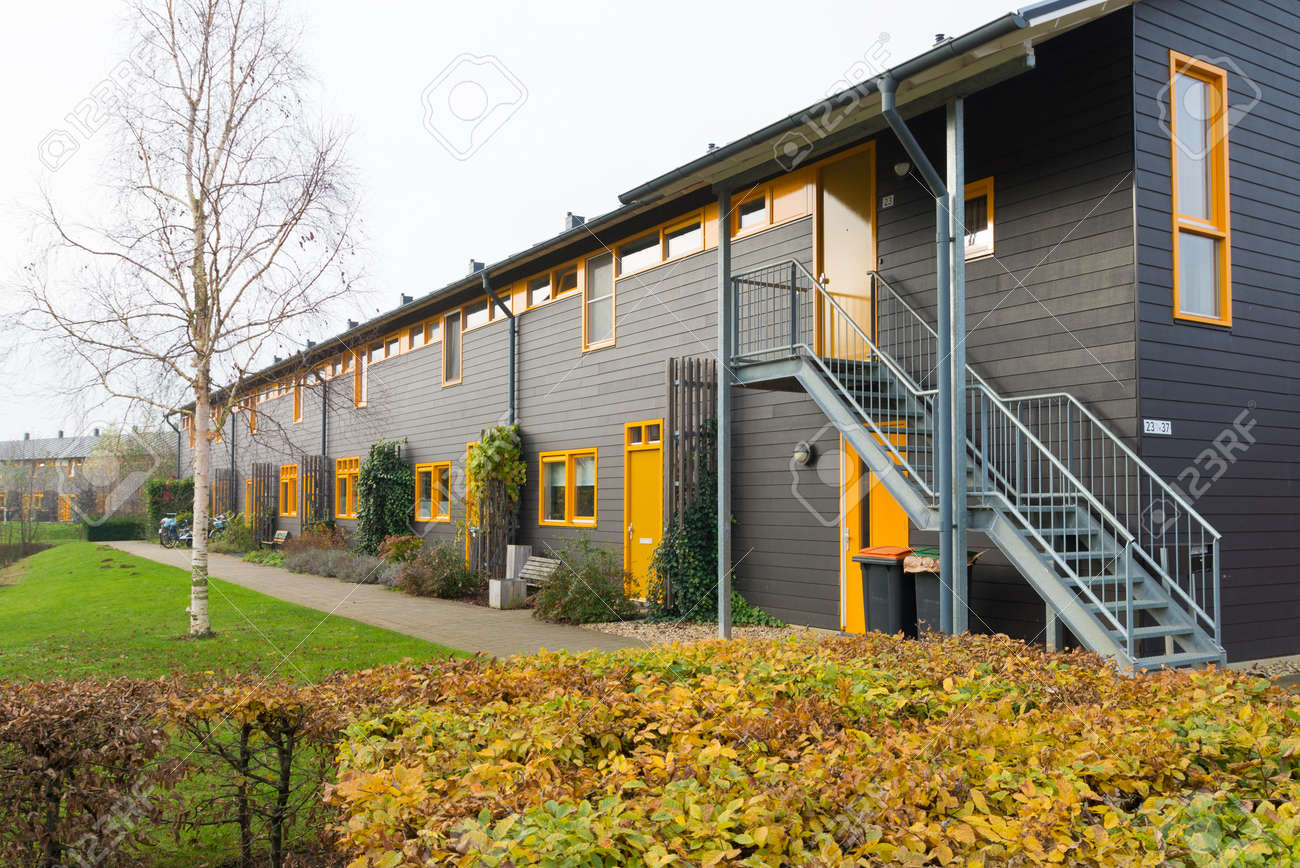 Exterior Of Newly Build Townhomes With Yellow Doors And Windows Stock Photo    42902946
