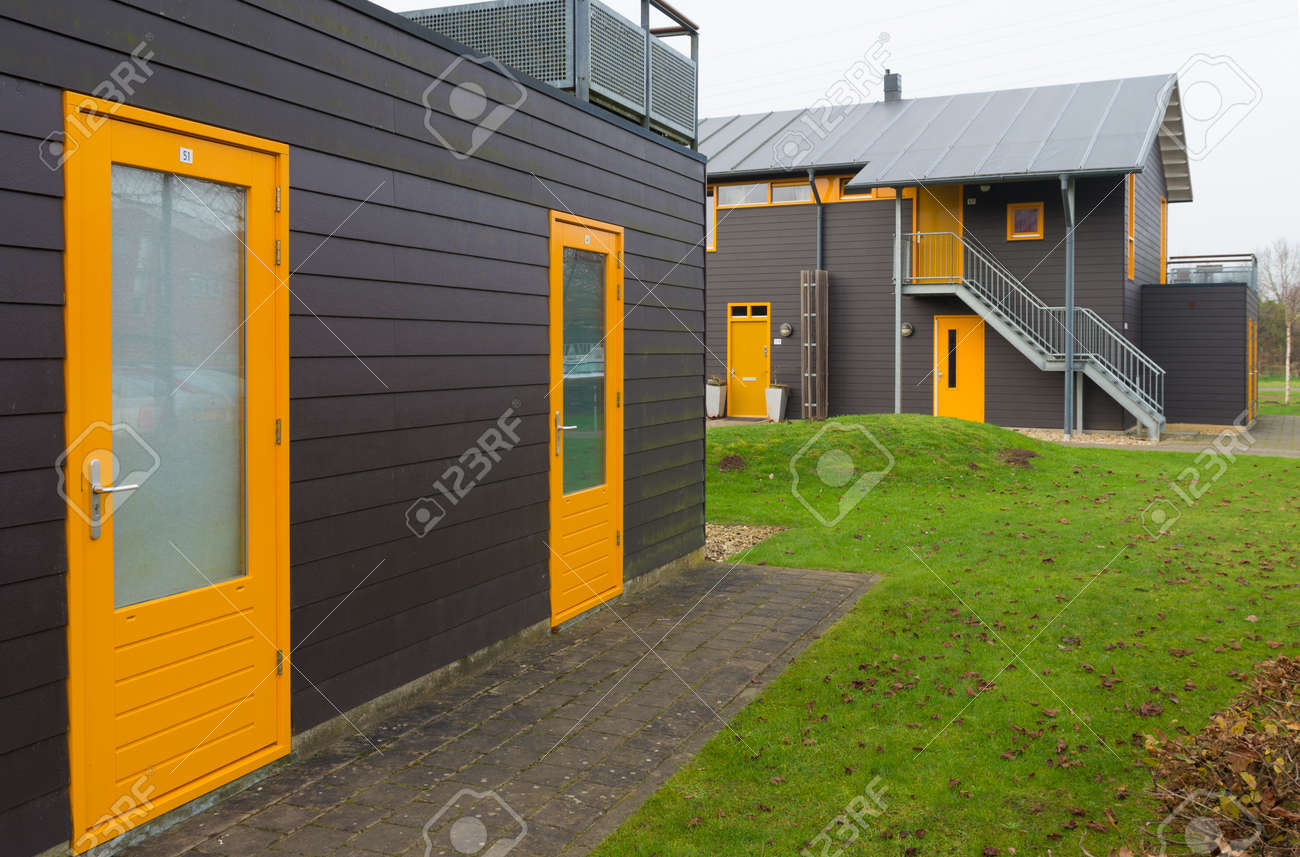 Exterior Of Newly Build Townhomes With Yellow Doors And Windows Stock Photo    42950601