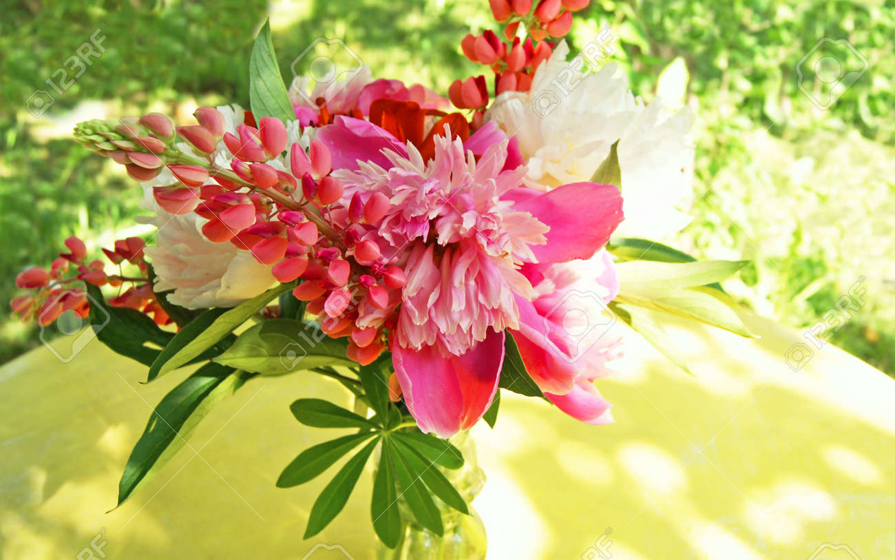 Bunch of pink peony flowers with lupine clusters on yellow table bunch of pink peony flowers with lupine clusters on yellow table in the garden stock photo dhlflorist Images