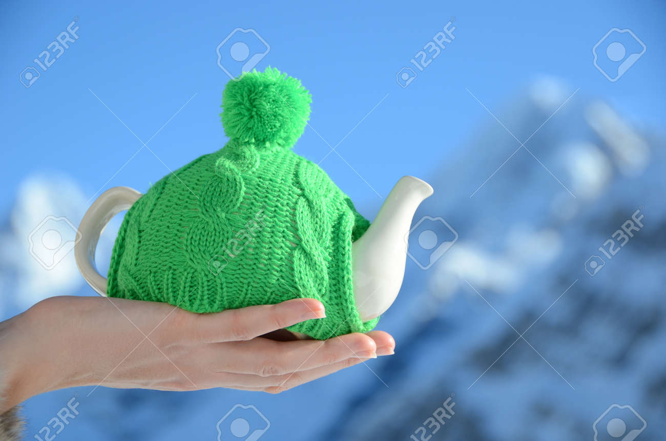 Tea pot in the knotted cap in the hand against alpine scenery Stock Photo - 18622716
