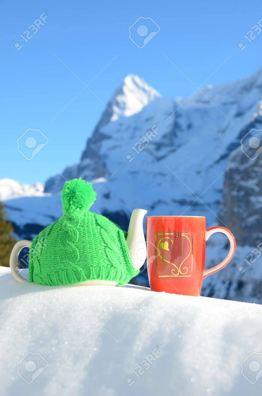 Tea pot in the cap and a cup against alpine scenery Stock Photo - 22671873