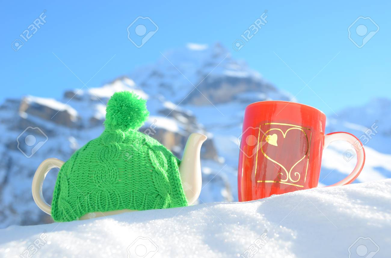 Tea pot in the cap and a cup against alpine scenery Stock Photo - 22671875