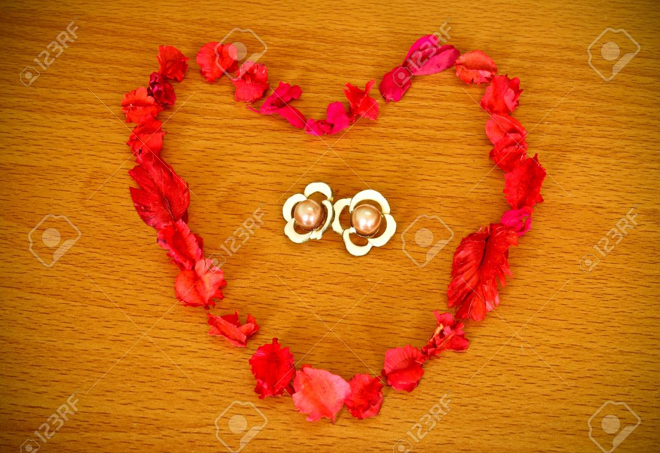 Dry flower heart with earrings on wood background Stock Photo - 9858647