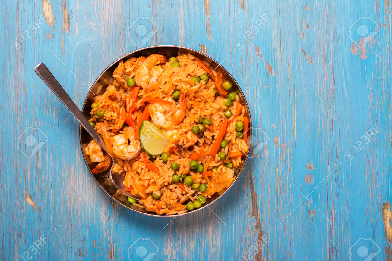 Traditional spanish paella dish with seafood, peas, rice and chicken over grunge blue background. Top view. Selective focus - 57183740