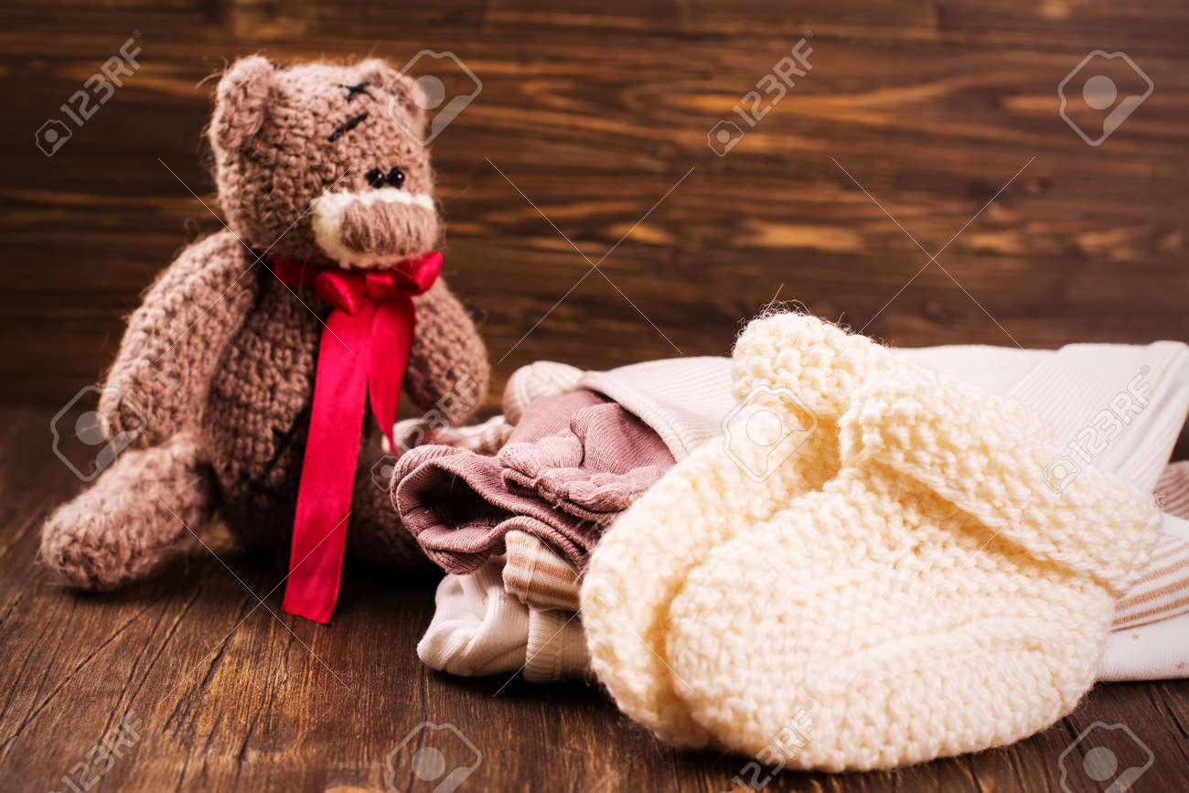 Banque d\u0027images , Tas de vêtements de bébé avec un ours en peluche. Carte  de voeux de douche de bébé. Style vintage