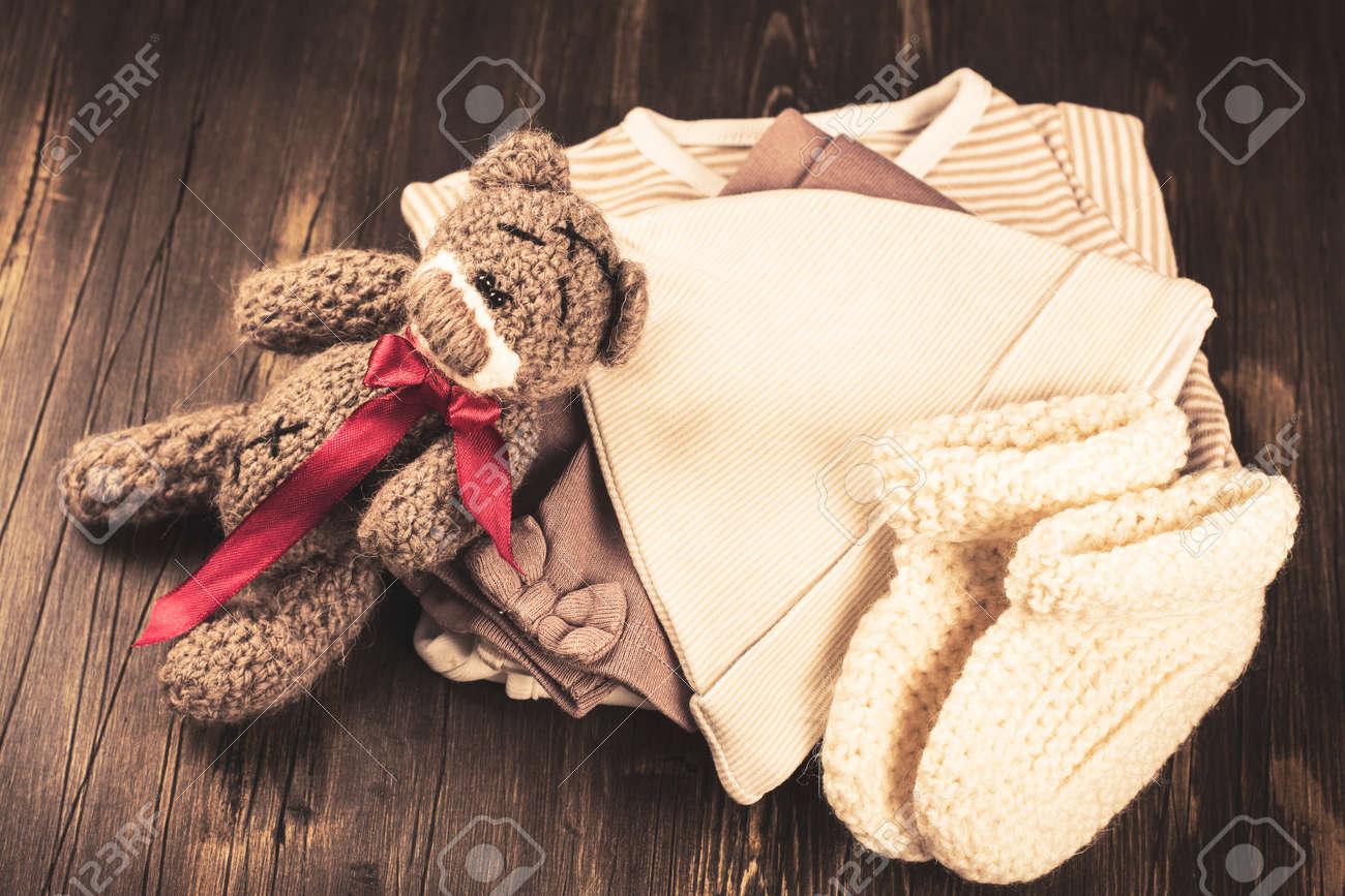 Banque d\u0027images , Pile de vêtements de bébé avec un ours en peluche. Bébé  carte de voeux douche. Style vintage