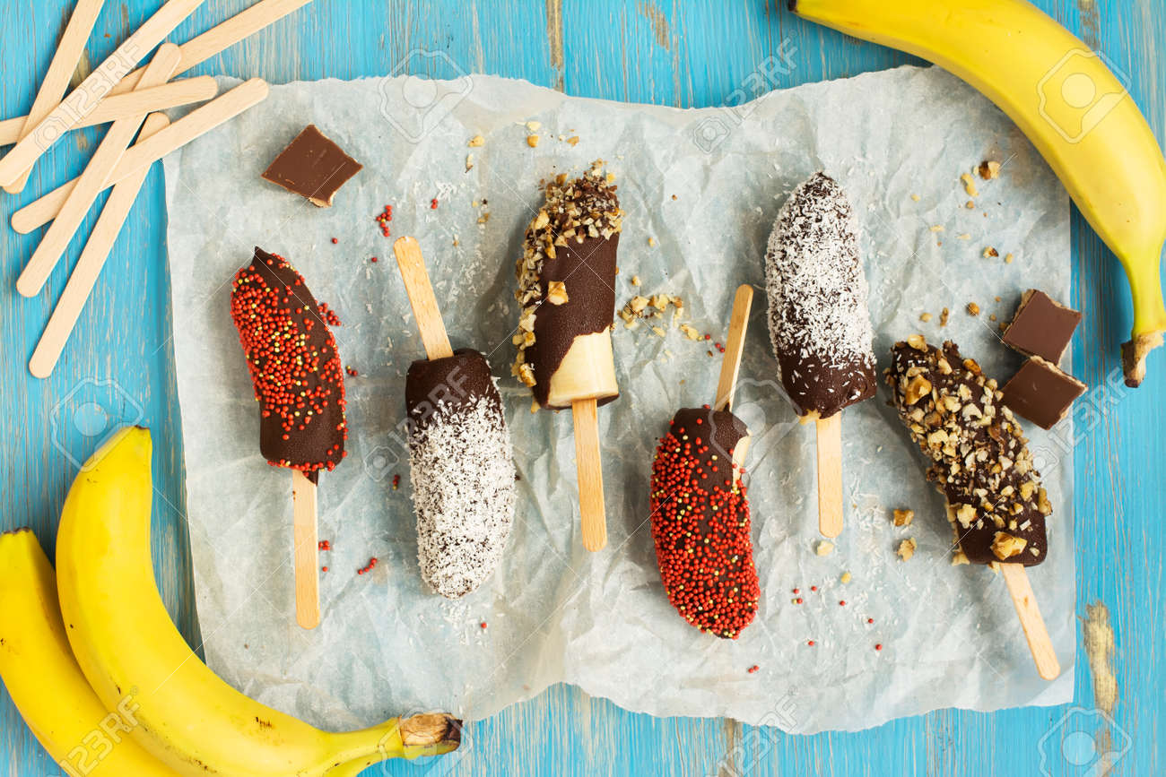 Frozen homemade banana pops covered with chocolate, sprinkles, nuts and coconut chips. Top view - 60523837