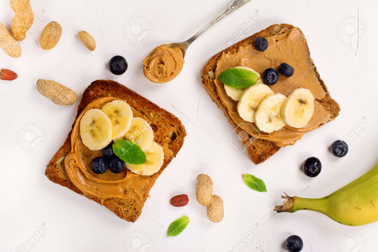 Peanut butter sandwiches with bananas and blueberry. Top view. Space for text - 60524079