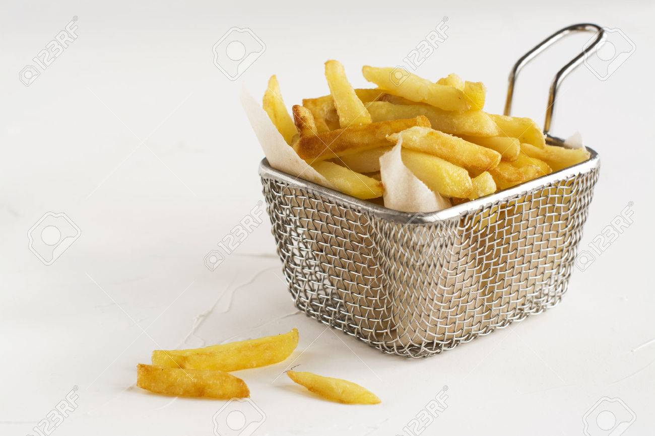 French fries in metal wire basket over white kitchen table. Selective focus - 60524171