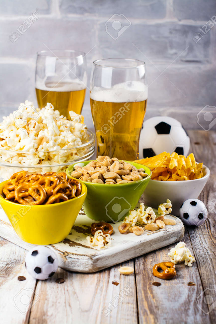 beer and snacks on wooden table football season or fans party
