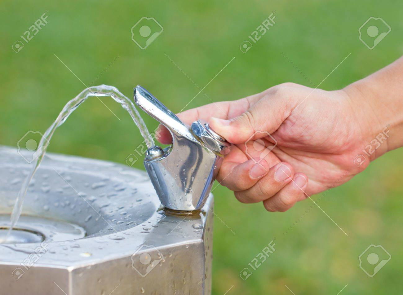 drinking water dispenser faucet. Man s hand turns on the drinking water faucet at public park Stock Photo  21353880Man S Hand Turns On The Drinking Water Faucet At Public Park Dispenser Polished chrome contemporary
