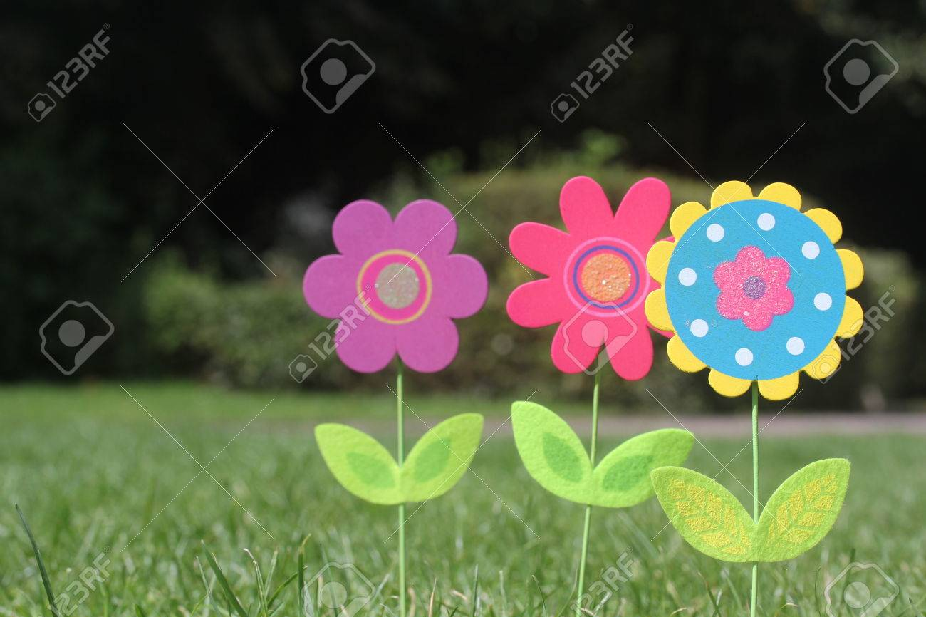Colorful flowers with green leaves stand in green grass of a stock colorful flowers with green leaves stand in green grass of a garden three beautiful unique izmirmasajfo